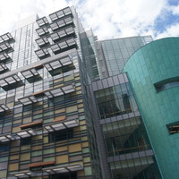 Image: A modern multi-storey building with multiple coloured wall panels and an oval conical tower at one corner