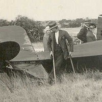 Image: A group of people examine the wreckage of a crashed biplane, including a man using crutches