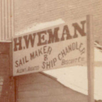 Image: A group of six men of various ages in Victorian attire stand in front of a shop. A painted banner on the top of the shop reads 'Hy. Weman. Sail Maker & Ship Chandler'