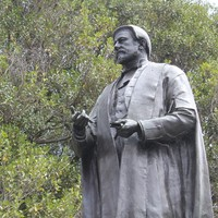 Bronze statue of standing man wearing robes