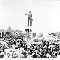 Image: crowd of people around bronze statue of man pointing