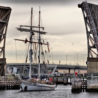 Image: A two-masted sailing vessel passes through a drawbridge on a cloudy morning. Another bridge crossed by modern auto-mobiles is visible in the background