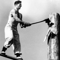 Image: man holding large axe standing on wooden plank embedded in large wooden post