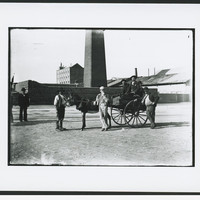 A group of men with cart standing outside the masonry perimeter wall of the copper smelter