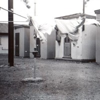 Image: clothesline in front of small, corregated iron buildings.