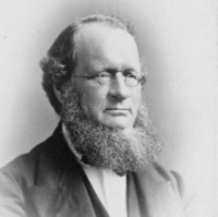 Image: Black and white photographic portrait of a man with small round glasses and a large beard