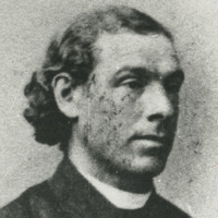 Image: A photographic head-and-shoulders portrait of a young Caucasian man in a Victorian-era Catholic clergyman's outfit. The man has long, dark wavy hair pulled back behind his head