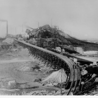 Image: railway tracks approaching slag heap with chimneys and large steel structures visible