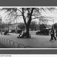 Image: view of people and cars along a street
