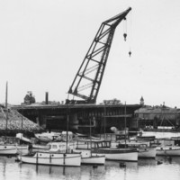 Image: A large derrick crane sits adjacent to one approach to a concrete bridge span. The other half of the bridge, also under construction, is visible in the background