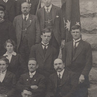 Image: A large group of Caucasian men and women in early Edwardian attire pose for a photograph in front of a large stone building. They are flanked by an Australian flag and British Union Jack
