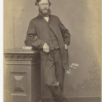 Image: bearded man in suit leaning against pedestal with book on it