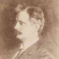 Image: A photographic head-and-shoulders portrait of a young man wearing a late-Victorian era suit and sporting a dark, handlebar moustache