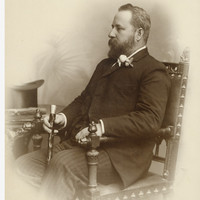 Image: caucasian man with beard holding a cane poses for photograph in chair