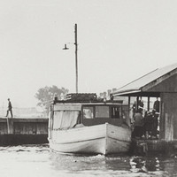 Image: A wooden motor boat with large cabin is moored alongside a jetty with a covered shelter. Several people are transiting from the jetty to the boat