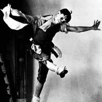 Image: A man in stage make-up and costume dances on a stage with arms outstretched