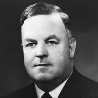 Image: A photographic head-and-shoulders portrait of a middle-aged Caucasian man with dark hair. He is clean-shaven and wearing a 1930s-era suit and tie