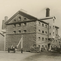 Image: A rectangular five-storey building with peaked roof sits on the edge of a dirt road. People and two horse-drawn carts stand in front of and around the building