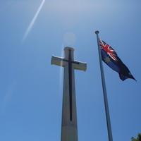 Image: Australian flag in front of cross monument, 2015.