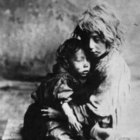 Image: two children in rags holding each other