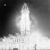 Image: A large, two-storey building with a tall clock tower in one corner is brilliantly lit at night. A small number of people on the street below look at the building