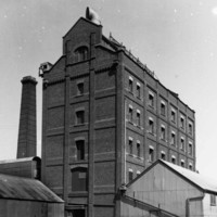 Image: A large, six-storey brick building with several windows on each floor and a large ventilation intake on its roof. Corrugated metal sheds stand in front and to the right of the building