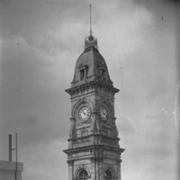 Image: A tall stone clock tower with an ornate roof and flagpole at its peak