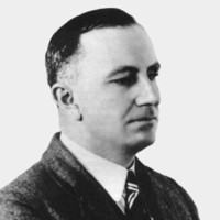 Image: A photographic head-and-shoulders portrait of a man wearing a suit with a striped tie