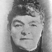 Image: Black and white headshot of woman wearing a fascinator