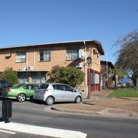 Image: suburban street with block of flats and several parked cars