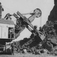Image: two men operating large machinery inf fron of pile of boulders