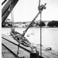 Image: large metal anchor suspended over jetty