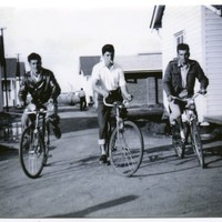 Image: three men riding bicycles between buildings