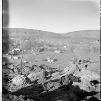 Image: man sitting on rocky outcrop overlooking township