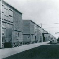 Image: row of tin buildings with car parked on dirt road