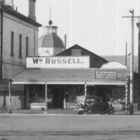 Image: A small, single-storey shop is sandwiched between two large multi-storey buildings. A sign above the shop's front door reads: 'Wm. Russell'