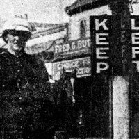 Image: A Caucasian man in an early twentieth century police uniform stands next to a marker with the words 'Keep' and 'Left' painted on it in large block letters