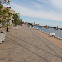 Paved waterfront with bollards along wharf