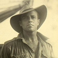 Image: Upper body portrait photograph of a man wearing a shirt with sleeves rolled up, and a large wide brimmed hat