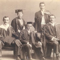 Image: Four men and a woman in university graduation attire sit on chairs and pose for a photograph