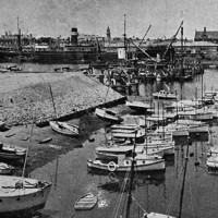 Image: A bridge under construction extends across a river in an active port. Several sail-boats and other small watercraft are moored within a basin in the foreground