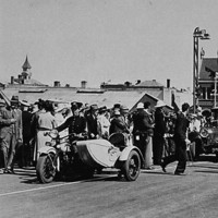 Image: A procession of 1940s-era cars escorted by a policeman on a motorcycle travels through a crowd of people gathered on the approach to a bridge