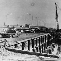 Image: Large cranes dismantle an old bridge span over a narrow river. Cars drive across a new bridge located a short distance and parallel to the old one