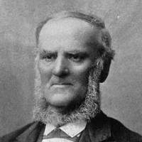 Image: A photographic portrait of a middle-aged balding man in Victorian attire. He is sporting a long chin-beard