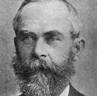 Image: A photographic portrait of a middle-aged man in late-Victoran attire with a salt-and-pepper beard and thinning hair