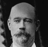 Image: A photographic head-and-shoulders portrait of a balding, middle-aged man with a goatee. The man is wearing an Edwardian-era suit and tie