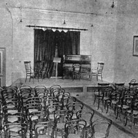 Image: A large, open hall with a stage at one end. Several rows of chairs face the stage, which features additional chairs, a music stand, and a piano