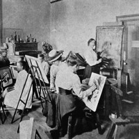 Image: A group of women in Edwardian attire paint at easels in a large, open room