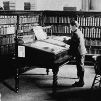 Image: A small group of men in a book-filled library read from desks