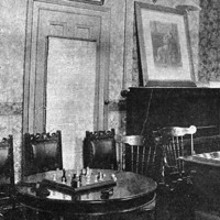 Image: Three chess tables with chairs stand in a room decorated with wallpaper and framed portraits